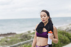 Beautiful fitness athlete woman resting drinking water after workout Stock Images