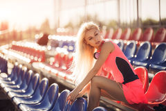 Beautiful fitness athlete woman resting after work out exercising on beach summer evening in sunny sunshine outdoor. Portrait Royalty Free Stock Photography