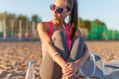 Beautiful fitness athlete woman wearing sunglasses listening music resting after work out exercising on summer evening stock photos