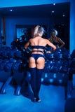 Beautiful fitness bikini model standing neat rack with dumbbells Royalty Free Stock Photos