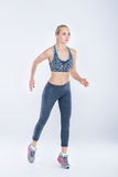 Beautiful fitness blonde girl in sports clothes runs on gray background Stock Images
