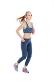 Beautiful fitness blonde girl in sports clothes runs on white background. Beautiful fitness blonde girl in sports clothes runs on a white background royalty free stock photo