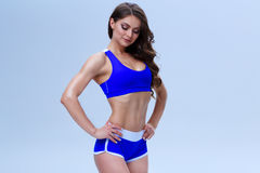 Beautiful fitness girl in a blue sport underwear is posing on a white background Royalty Free Stock Photo