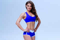 Beautiful fitness girl in a blue sport underwear is posing on a white background Stock Image