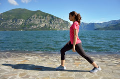 Beautiful fitness girl doing exercises in lake landscape. Girl doing yoga exercise in lake. Royalty Free Stock Photos
