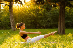 Beautiful fitness girl exercising in nature on sunny summer day.  Royalty Free Stock Images