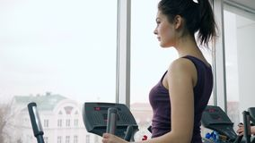 Beautiful fitness girl exercising on simulator in gym