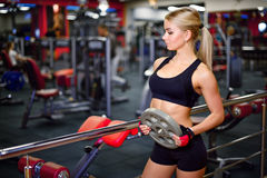 Beautiful fitness girl holds Bumper Plates for training in the gym, looking in the direction the background is Stock Images