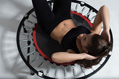 Beautiful fitness-girl make exercises on rebounder Stock Photos