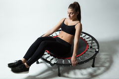 Beautiful fitness-girl make exercises on rebounder Stock Image