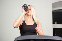 Beautiful fitness girl running and drinking water on treadmill at the gym Royalty Free Stock Photo