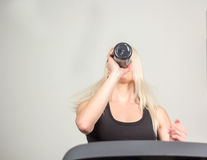Beautiful fitness girl running and drinking water on treadmill at the gym Royalty Free Stock Images