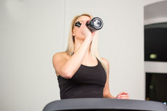 Beautiful fitness girl running and drinking water on treadmill at the gym Stock Photography
