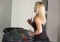 Beautiful fitness girl running on treadmill at the gym Royalty Free Stock Photos