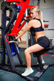 Beautiful fitness girl sitting on the exercise equipment for legs, looking in the direction the background is Stock Images