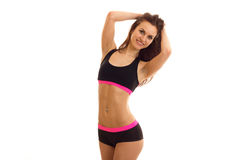 Beautiful fitness girl sporting short shorts and top smiles and keeps hands near hair Royalty Free Stock Image