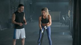 Beautiful fitness girl with trainer are doing training using crossfit rope. Workout at the gym. 4K slow motion