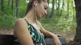 Fit girl lost in thoughts, relaxing on a bench, choosing song from phone. Girl with earphones. Beautiful fitness girl using mobile phone outdoors, sitting on a stock video footage