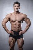 Beautiful fitness male model posing in studio on white grey back Stock Photo