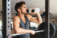 Beautiful fitness man with weights drinking water. After training stock photography