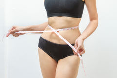 Beautiful fitness model measures the waist on white background,h Royalty Free Stock Image