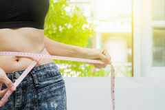 Beautiful fitness model measures the waist on white background,h Royalty Free Stock Photography