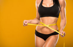 Beautiful fitness model measures the waist on a yellow Royalty Free Stock Photography