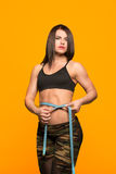 Beautiful fitness model measures the waist on a yellow Royalty Free Stock Image