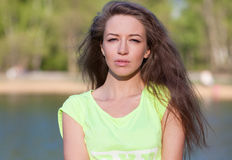 Beautiful Fitness the model in a Top Costs on the bank of the Lake in the Summer on a sunset. Royalty Free Stock Photography