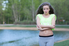 Beautiful Fitness the model in a Top Costs on the bank of the Lake in the Summer on a sunset. Blowing Long Hair. Fitness abs Stock Photos