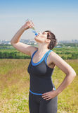 Beautiful fitness plus size woman drinking water Royalty Free Stock Images