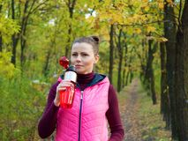 Beautiful fitness sport girl in autumn park in sportswear drinks water or isotonic drink from a sports bottle. Beautiful fitness sport girl in autumn park in Stock Photos