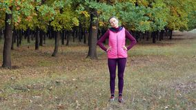 Beautiful fitness sport girl does warm up before running in autumn park. Workout outdoors. stock footage