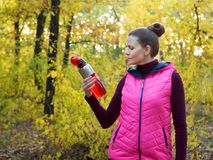 Beautiful fitness sport girl in sportswear with sports water bottle or isotonic drink in hand in autumn forest. Beautiful fitness sport girl in sportswear with Stock Photos
