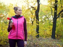 Beautiful fitness sport girl in sportswear with sports water bottle or isotonic drink in hand in autumn forest. Beautiful fitness sport girl in sportswear with Royalty Free Stock Photography