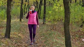 Beautiful fitness sport girl walking along the autumn park in sportswear with sports water bottle or isotonic drink in stock video footage