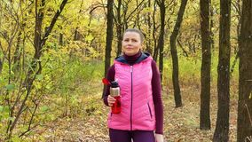 Beautiful fitness sport girl walking along the autumn park in sportswear with sports water bottle or isotonic drink in hand.