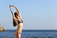 Beautiful fitness woman body wearing a swimsuit on the beach. Beautiful fitness woman body posing wearing a swimsuit on the beach with the sea and the horizon in Royalty Free Stock Photography