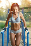 Beautiful fitness woman doing exercise on parallel bars sunny outdoor. Sporty girl doing push ups on bars outdoor stock photo