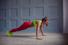Beautiful fitness woman is doing push-ups in the gym, stock photo