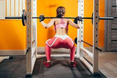 Beautiful fitness woman lifting barbell. Sporty woman lifting weights. Fit girl exercising building muscles. Back view. Stock Photos
