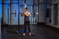 Beautiful fitness woman lifting barbell. Sporty woman lifting weights. Fit girl exercising building muscles. Fitness and Royalty Free Stock Photo