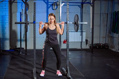 Beautiful fitness woman lifting barbell. Sporty woman lifting weights. Fit girl exercising building muscles. Fitness and Stock Photo