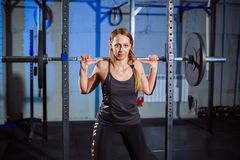 Beautiful fitness woman lifting barbell. Sporty woman lifting weights. Fit girl exercising building muscles. Fitness and Royalty Free Stock Image