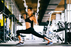 Beautiful fitness woman lifting dumbbells . Fitness sporty girl exercising in gym.  Royalty Free Stock Photos