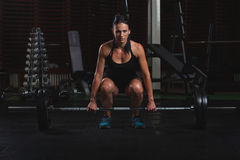 Beautiful Fitness Woman preparing to lift some heavy weights.Female Body builder practising in the gym Stock Image