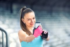 Beautiful fitness woman taking selfie with phone camera. Healthy woman training and taking pictures Stock Images