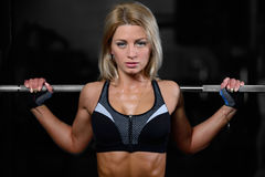 Beautiful fitness woman trains in the gym. Fitness strength training workout bodybuilding concept background - muscular bodybuilder sexy woman doing exercises in Stock Photos