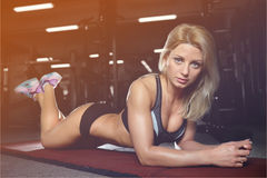 Beautiful fitness woman trains in the gym. Fitness strength training workout bodybuilding concept background - muscular bodybuilder sexy woman doing exercises in Royalty Free Stock Image