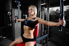 Beautiful fitness woman trains in the gym. Fitness strength training workout bodybuilding concept background - muscular bodybuilder sexy woman doing exercises in Stock Photo